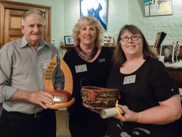"Last year's Marion Gebbie winner Russell Ball with the award, Kaye Taylor-Law and Sue Dilley with the winning piece ""Going North"""